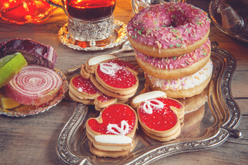 Fotobehang Bakkerij Colorful Christmas donuts and cookies on a wooden table in a rustic, cosy style.