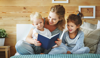 family mother reading to  children book in bed.