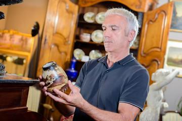 Man looking at antique vase