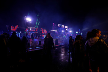 People walk near the attractions at the Winterville Christmas fairground on Clapham Common in London
