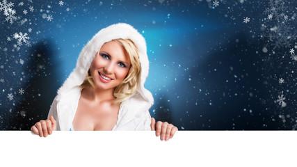 attaktive blonde Frau mit leerem Schild vor winterlichen Hintergrund