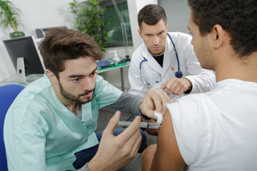 young internist doctor injecting a patient under surveillance