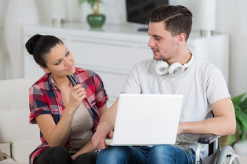 disabled man using laptop sitting next to his girlfriend