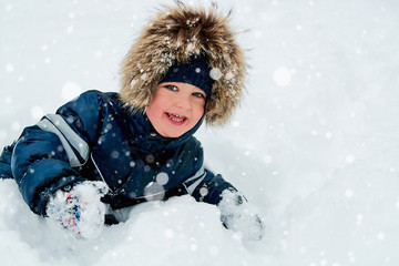 close-up portrait of a young beautiful blue-eyed boy playing in the snow for a walk in the winter park