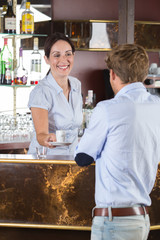 Woman serving coffee to man in cafe