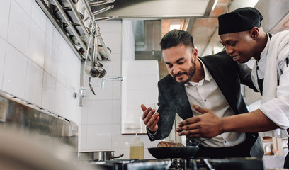 Manager smelling the aroma of food with chef