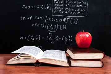 Apple and books on a wooden table and school blackboard with mathematical equations in the classroom