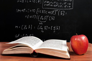 Book and Apple on wooden table in front of blackboard where is mathematical equation in the classroom