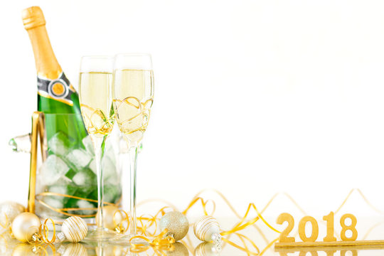 New Year Celebration with Champagne Glasses and a Bottle 2018. New Year flutes with bubbling champagne and a bottle on the white background.