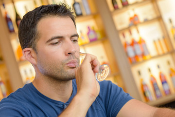 Man drinking from glass in alcohol store
