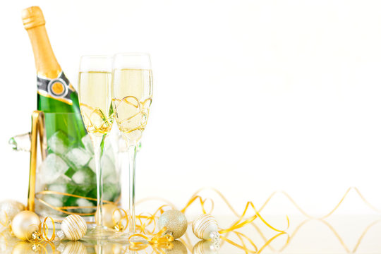 New Year Celebration with Champagne Glasses and a Bottle. New Year flutes with bubbling champagne and a bottle on the white background.