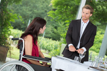woman in a wheelchair ready to order in a restaurant