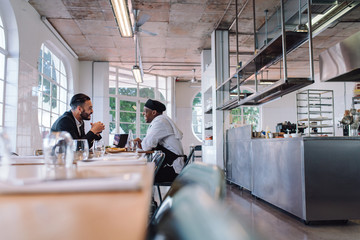 Business manager and chef talking in restaurant
