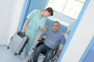 man in wheelchair leaving hospital