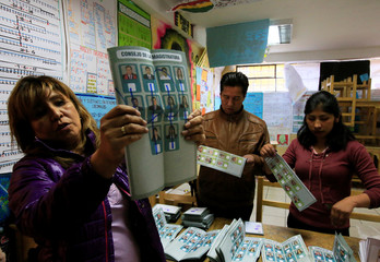 A member of the electoral committee shows a ballot that is marked null during the counting of votes in the nationwide judicial elections in La Paz, Bolivia