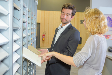 male and female business partners picking up folders on shelf