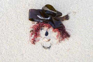 fille rousse au chapeau - dessin sur le sable des algues et des coquillages