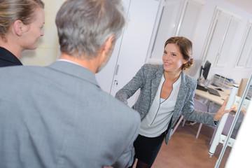 Female executive greeting couple