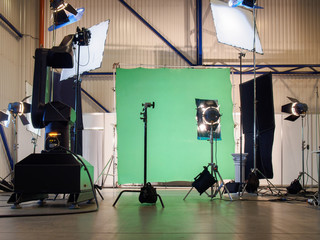 Real empty green screen film/photo studio with lighting/studio equipment