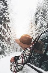 Pretty woman traveler hanging out of the car window and enjoying snowy landscape. Winter holidays. Wanderlust. Hipster wearing hat and checkered scarf