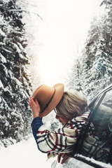 Beautiful hipster woman in hat and checkered scarf hanging out of the car window. Cute girl traveling on winter road in snow forest