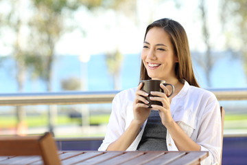 Woman holding a coffee mug in an apartment balcony