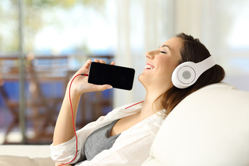 Girl listening music and showing phone screen indoors