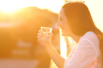 Happy lady holding a glass of water at sunset