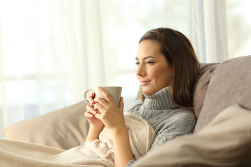 Tenant resting holding coffee on a couch