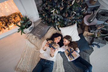 Merry Christmas and Happy Holidays. Cheerful mom and her cute daughter girl exchanging gifts. Parent and little child having fun near Christmas tree indoors. Loving family with presents in room.