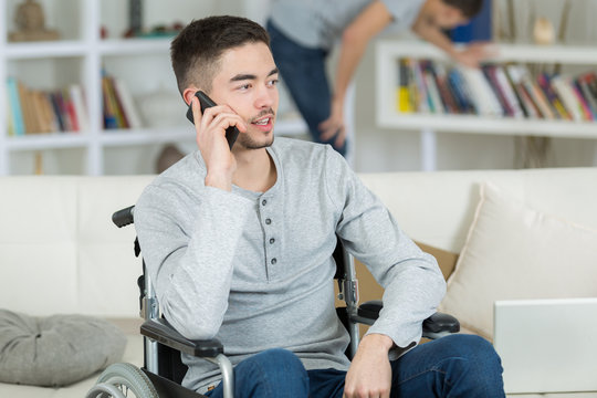 boy on the wheelchair using a cellular phone