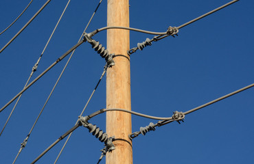 Close up of brand new wood pole and power lines in new development area with insulators against blue sky