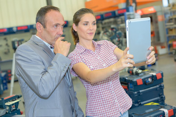 Man and woman in hardware store holding tablet