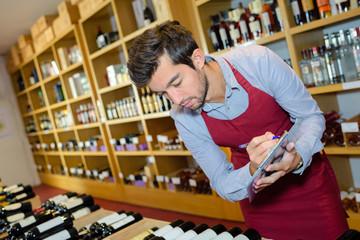 wine merchant recording stock on clipboard