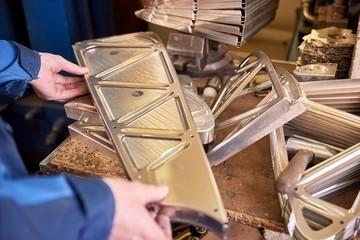 Hands of engineer, metal part. Stainless steel, workshop table.