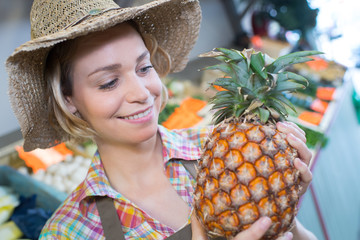Lady wearing straw hat and holding a pineapple