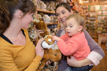 mother and friend playing with daughter in toy store