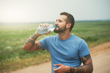bearded man drinking bottle of water