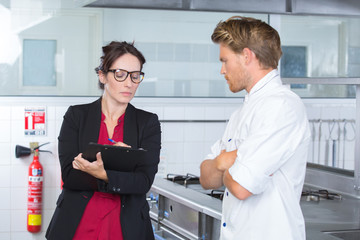 female inspector in restaurant kitchen with chef
