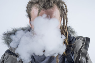 Man dreadlocks smoking electronic cigarette .