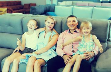 Family posing near new sofa