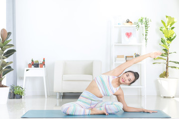 Asian beautiful sports woman performs the exercises at home .