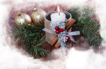Hot white candle  and a Christmas ball on a wooden background