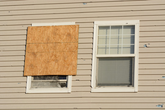 Boarded up window and hail storm damage on house siding and window frame