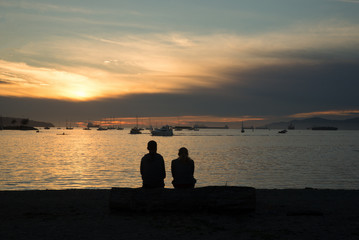 A silhouette of a couple sitting by the ocean and enjoying the sunset in Vancouver