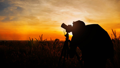 Photographers in meadow with silhouette.