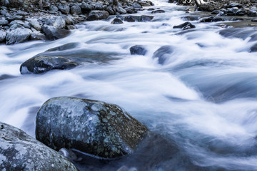 Swiftly moving river water over and around large rocks winter landscape, horizontal aspect