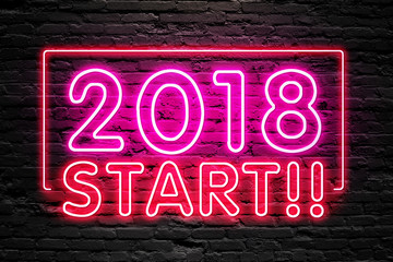 READY FOR 2018 NEW YEAR concept. 2018 START text fluorescent Neon tube Sign on dark brick wall. Front view. Can be used for online banner ads or background. night moment.