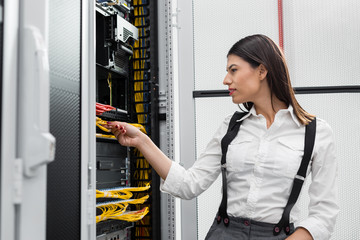 Young engineer businesswoman in network server room