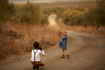 A boy photographer shoots a child in a park in a field on the road
